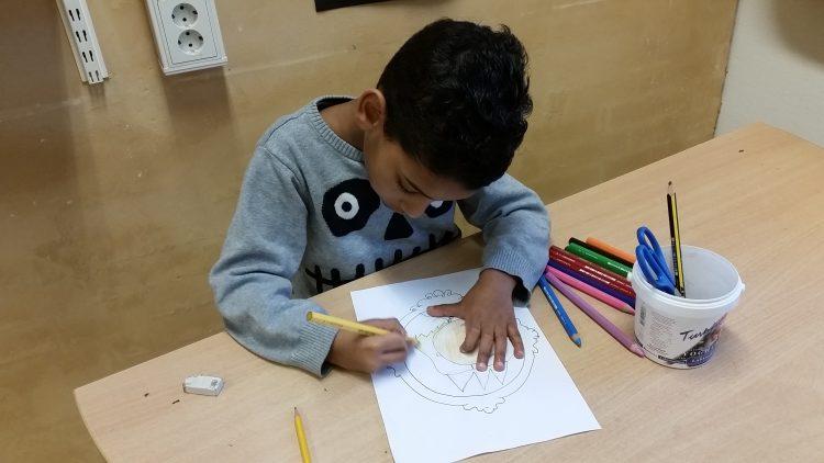 Ett barn färlägger en teckning.