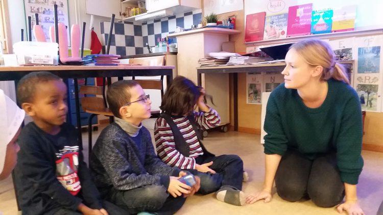 Pedagog lyssnar på tre barn.