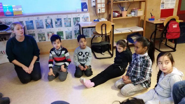 Pedagog sitter med barn på golv.