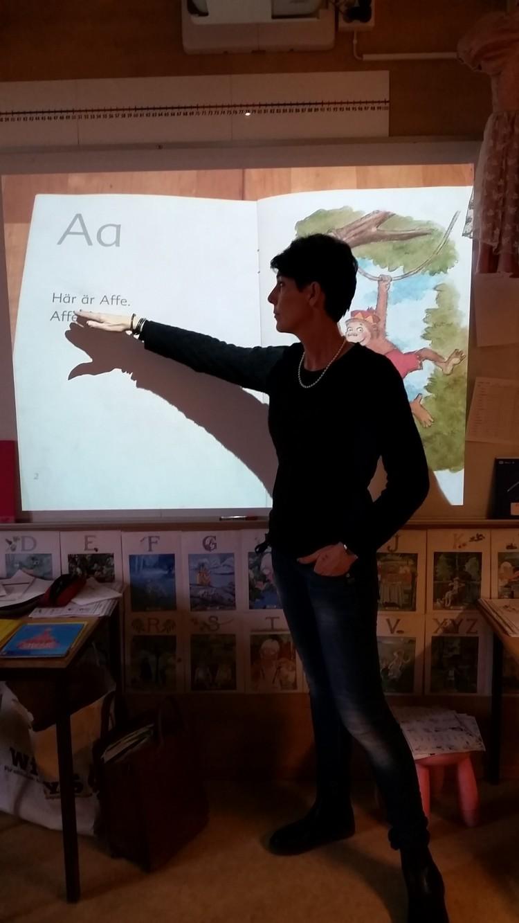 Pedagog pekar på en projicerad bild av ett A.