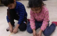 Barn pysslar på golvet.