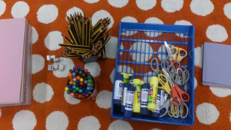 Pysselsaker på bord: pennor, saxar och papper.