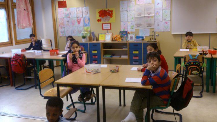 Barn i bänkar lyssnar på pedagog.