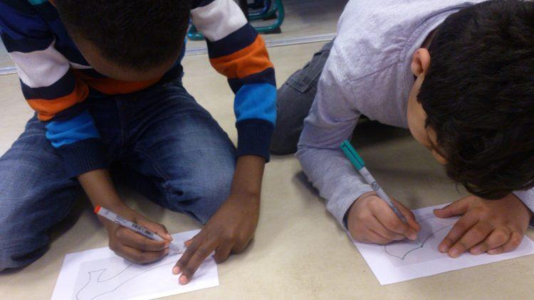 Två barn ritar skor.