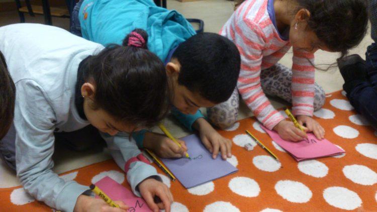 Tre barn hukar sig och skriver.
