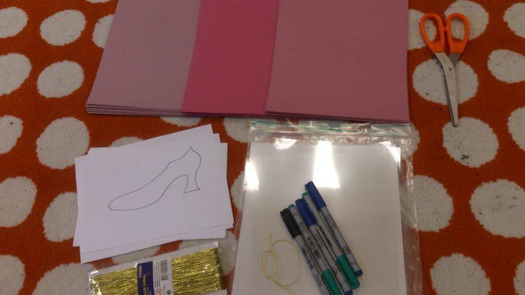 Papper, pennor och sax på ett bord.
