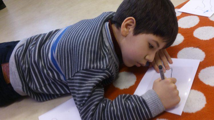 Ett barn ligger och ritar.