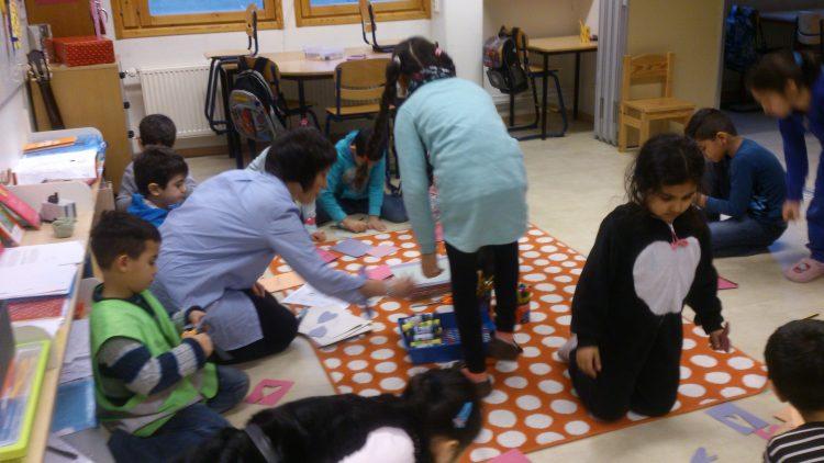 Barn sitter runt en prickig matta.