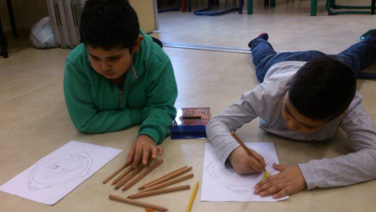 Två barn ligger och ritar.