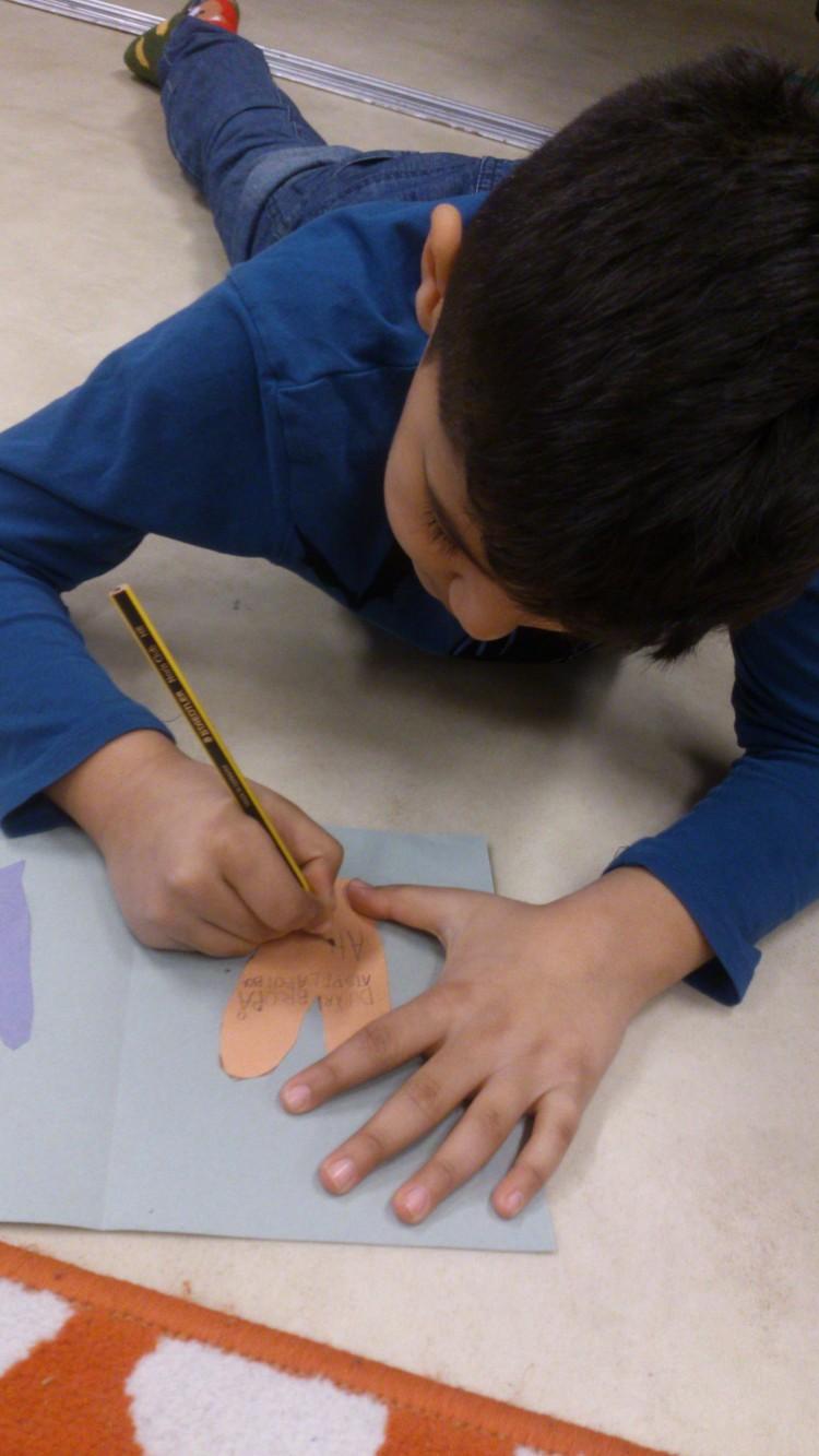 Barn skriver på ett fastklistrat hjärta.