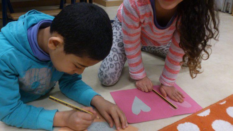 Två barn skriver Alla hjärtans dag-hälsningar.