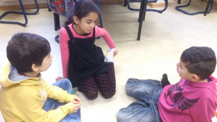Barn pratar på golvet.