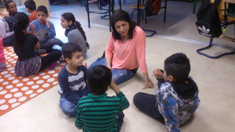 Pedagog sitter och pratar med barn på golvet.