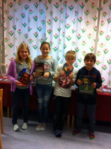 Fyra barn håller i varsin bok.
