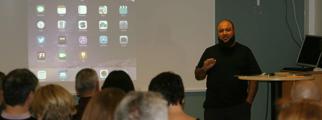 Abdul Chohan föreläser framför projicerad presentation.