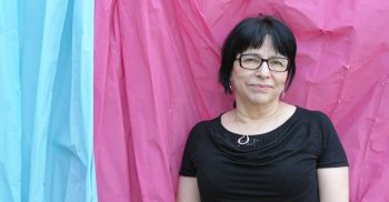 Kvinna framför skynke av rosa och blått tyg.