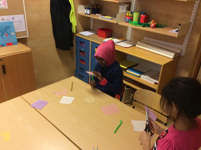Två barn pysslar vid bord.