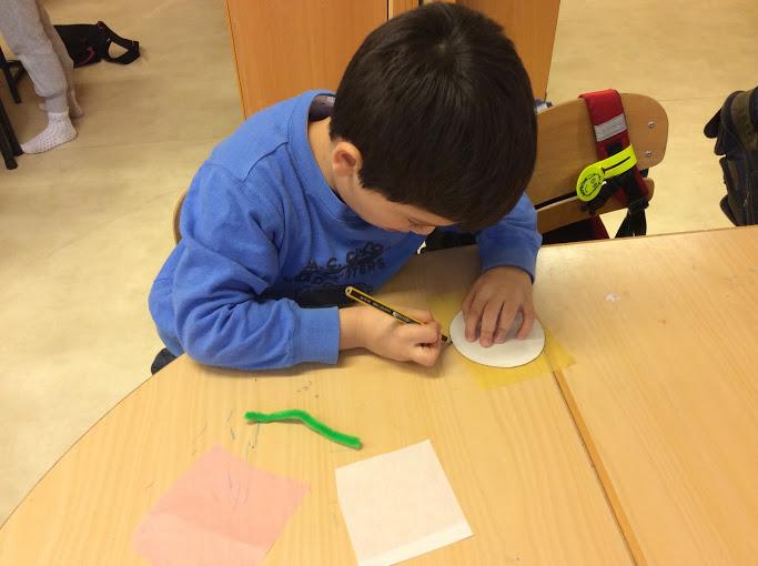 Ett barn pysslar vid bord.