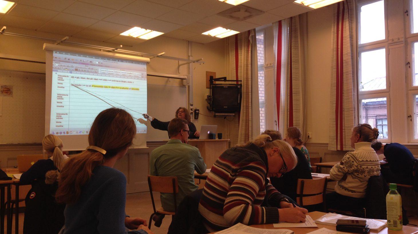 Kvinna pekar med pekpinne på presentation.