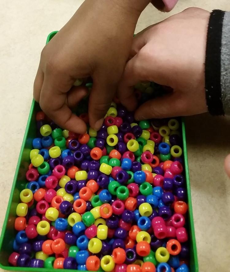 Händer tar pärlor i olika färger.