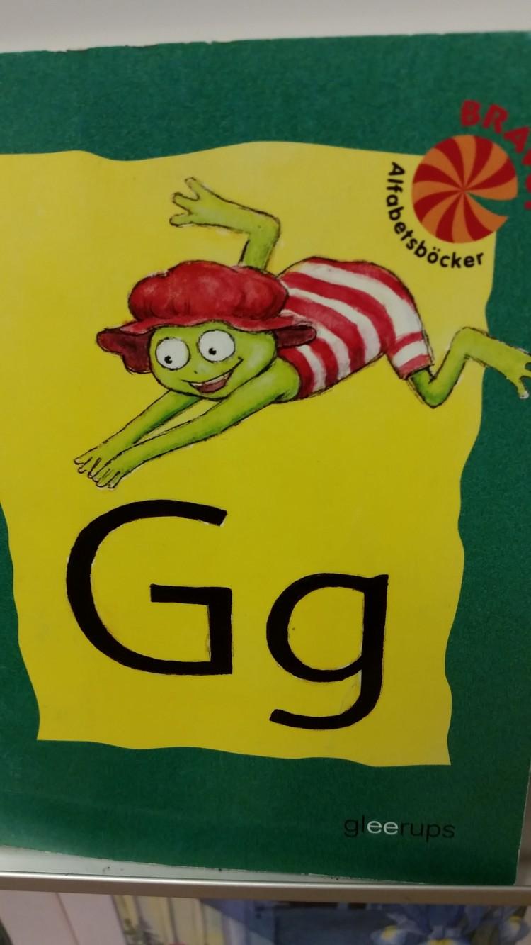 Bokstaven G på lapp med groda på.