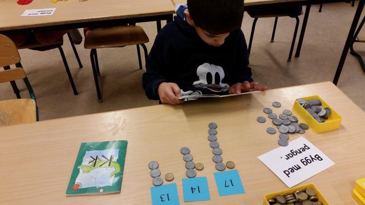 Elev jobbar med plastpengar och siffror.