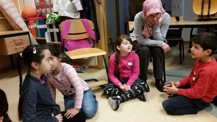 Elever sitter på golvet.