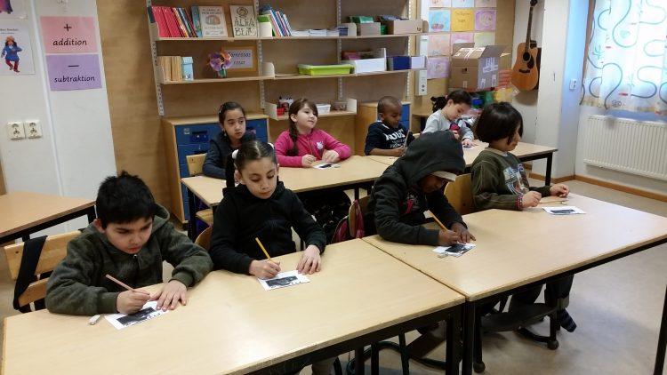 Elever sitter vid bänkar och arbetar.