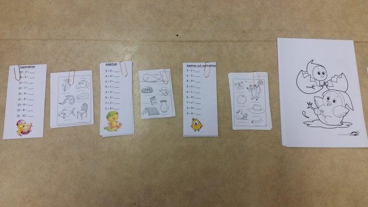 Papper med tal och tecknade kycklingar på.