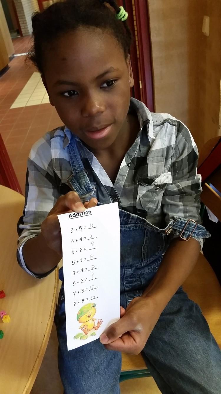 Barn håller upp lapp med lösta additiontal.