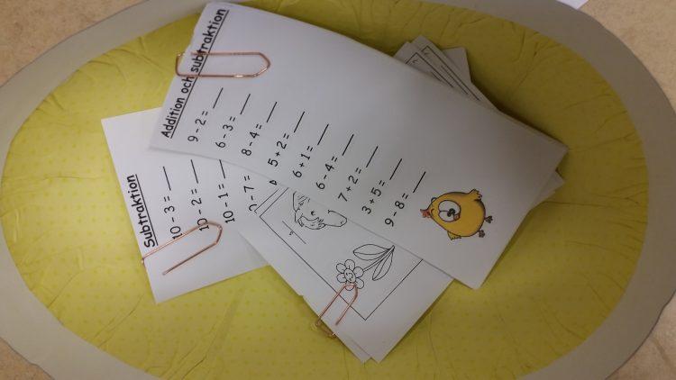 Papperslappar med plus och minus-tal skrivna på.