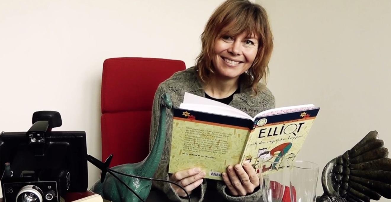 Kvinna sitter i röd fåtölj och läser bok.