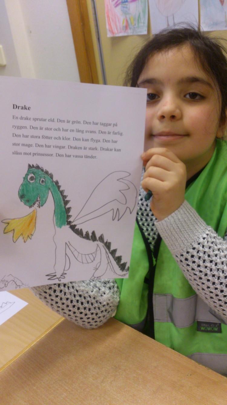 Barn håller upp teckning av en drake.