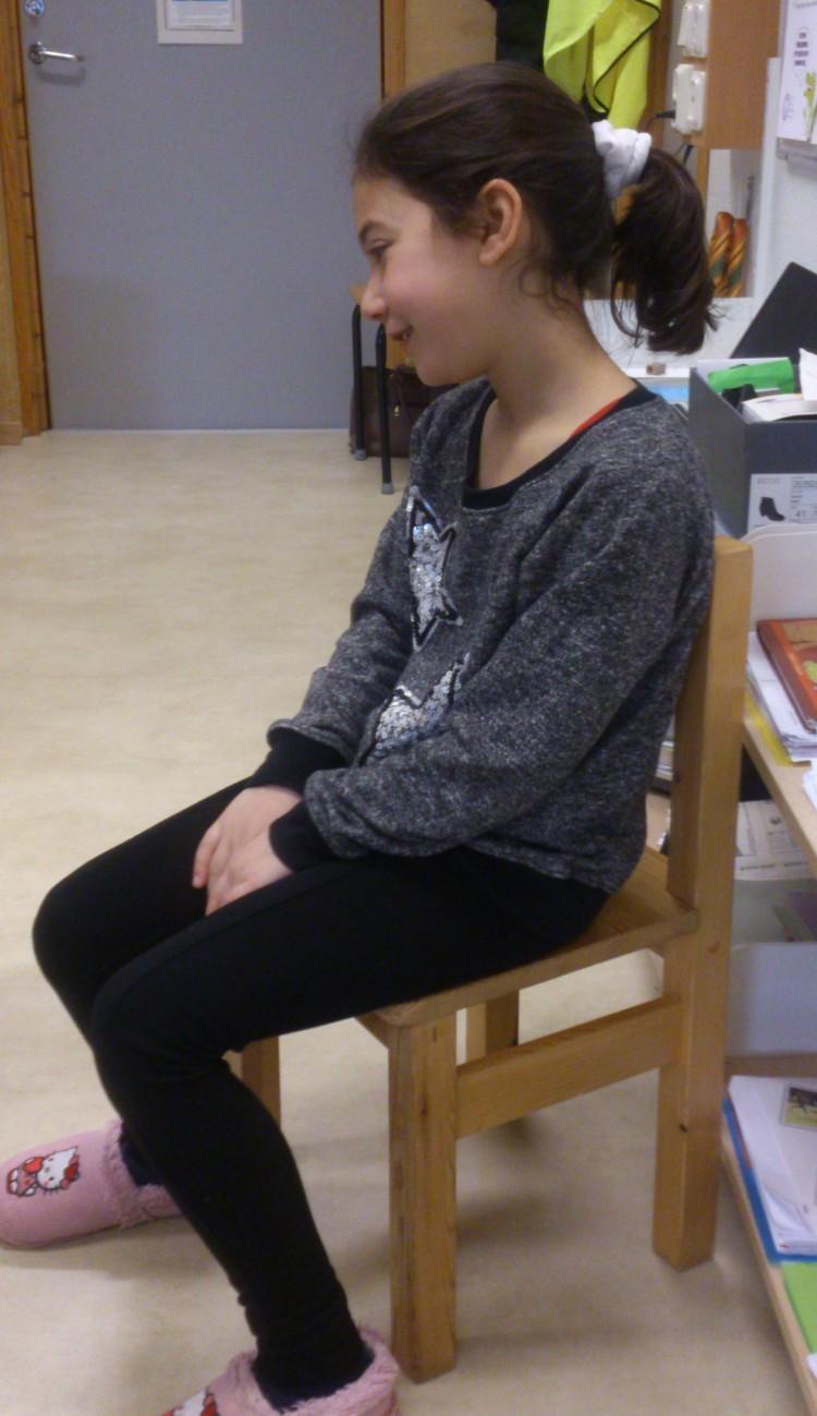 Elev sitter på stol.