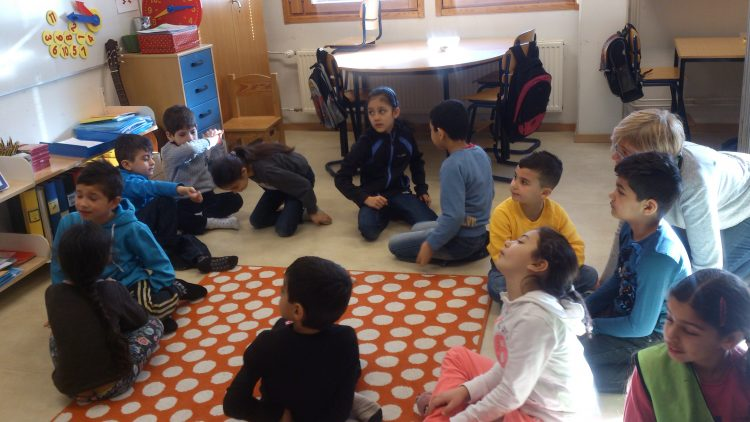 Barngrupp sitter på golvet.