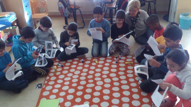 Elever sitter på golvet och klipper.