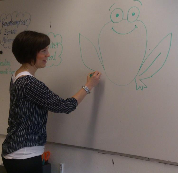 Lärare tecknar en groda på tavla.