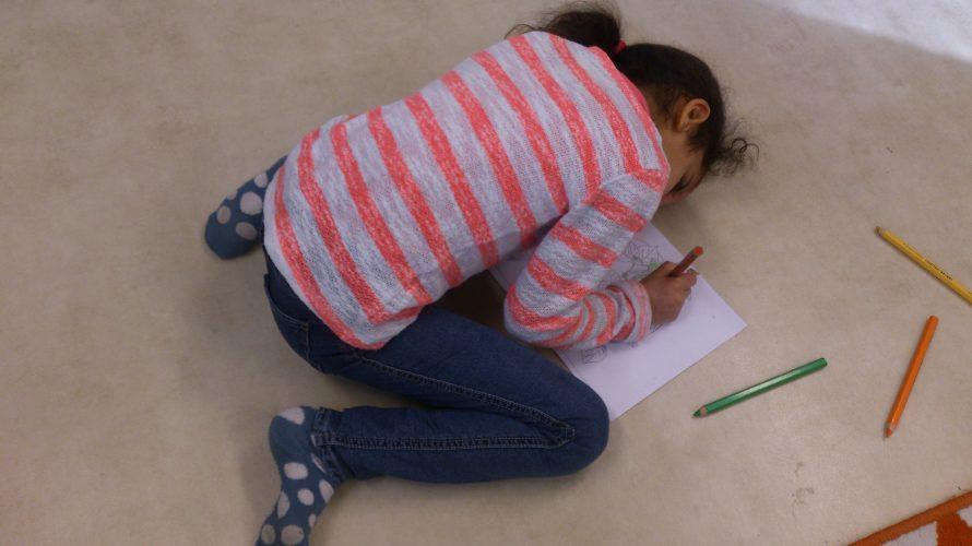 Elev sitter på golvet och ritar.
