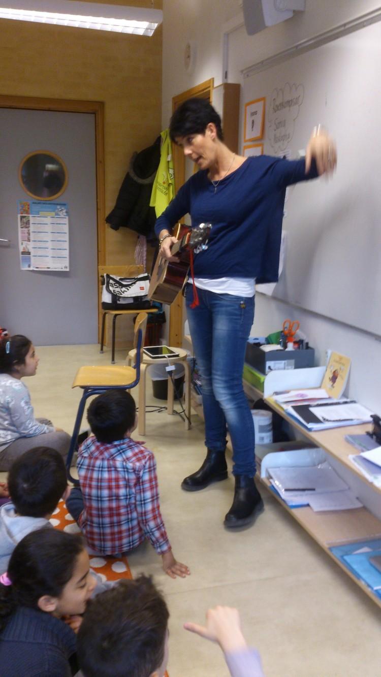 Lärare sjunger och spelar gitarr framför barngrupp.
