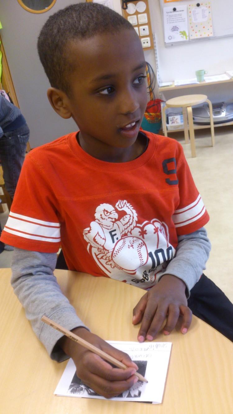Elev skriver på lapp om groda.