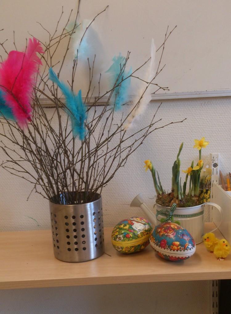 Påskris, påskägg, kycklingar och påskliljor står på bänk.