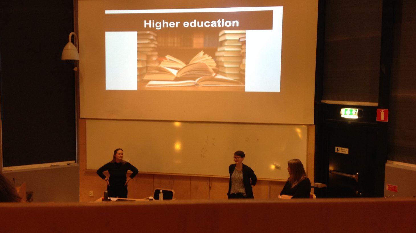 Tre kvinnor framför projicerad presentation.