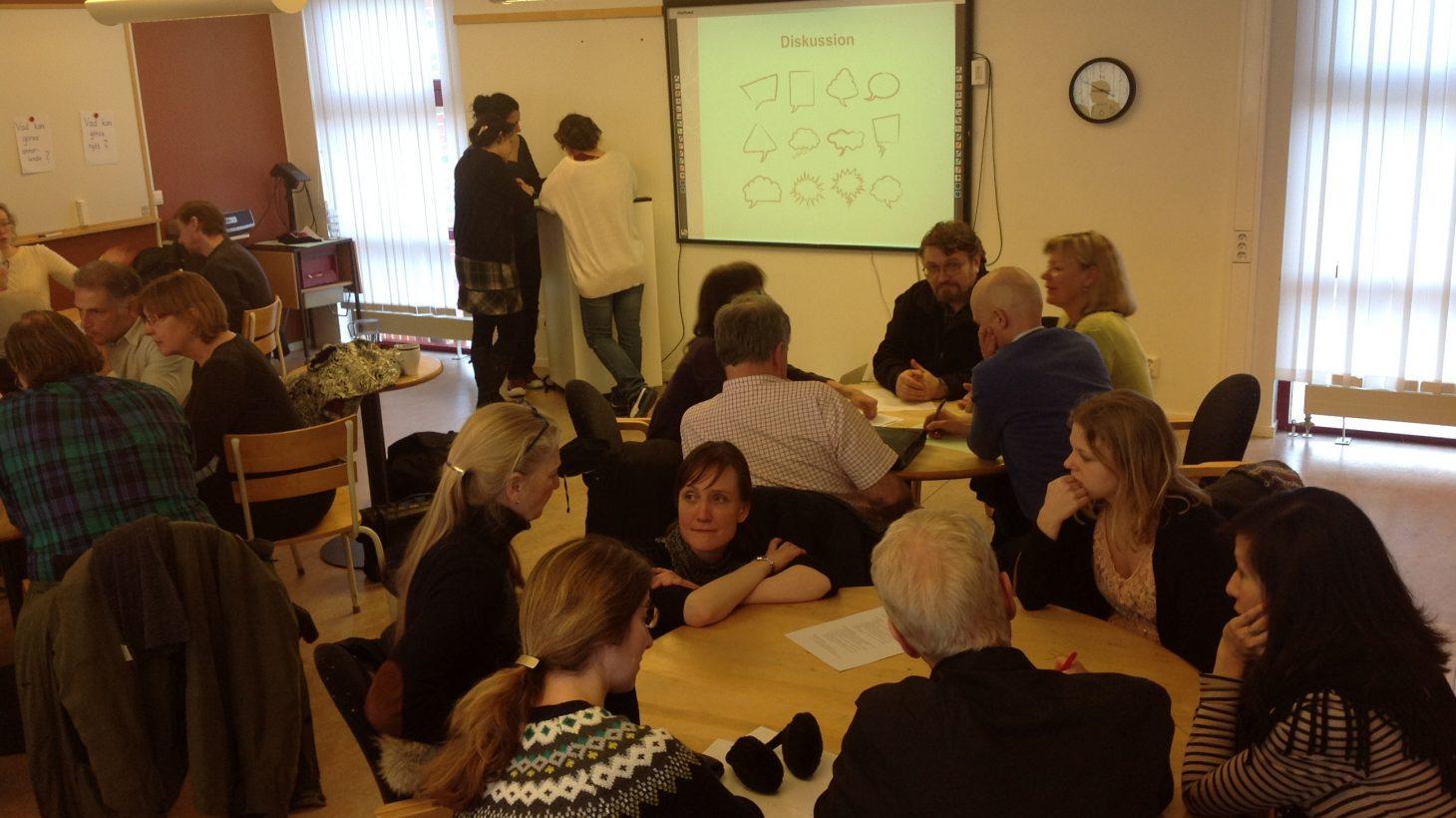 Lärare sitter runt runda bord.
