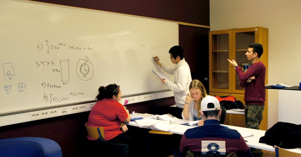 Person skriver på tavla medan en annan instruerar.