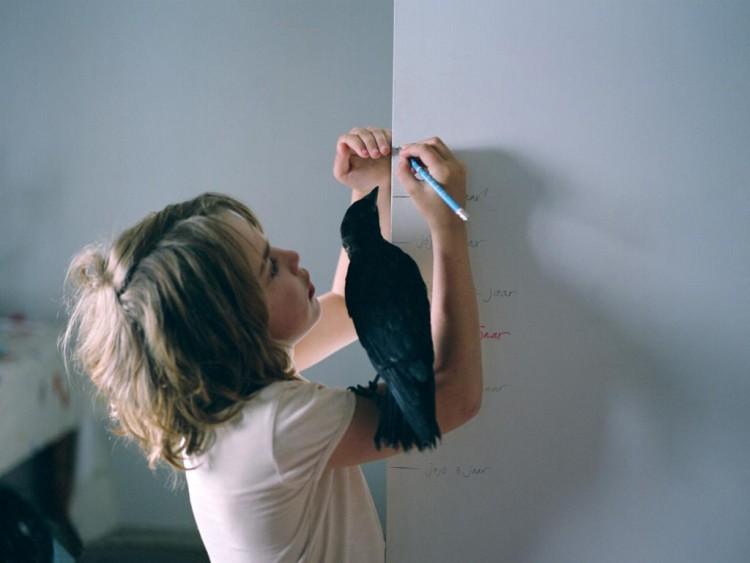 Barn med kråka på armen ritar på en vägg.