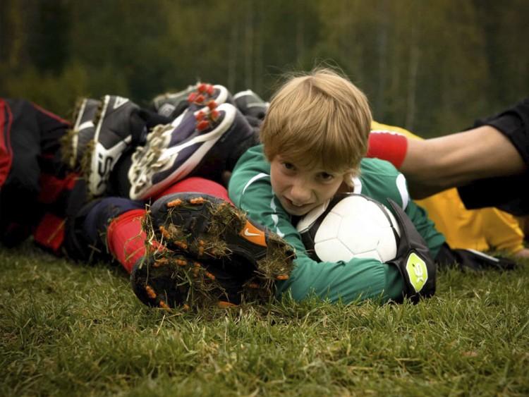 Pojke som ligger unders i hög av fotbollsspelare håller i fotboll.