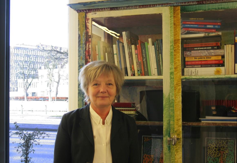 Maria Jarlsdotter framför stort skåp med böcker.