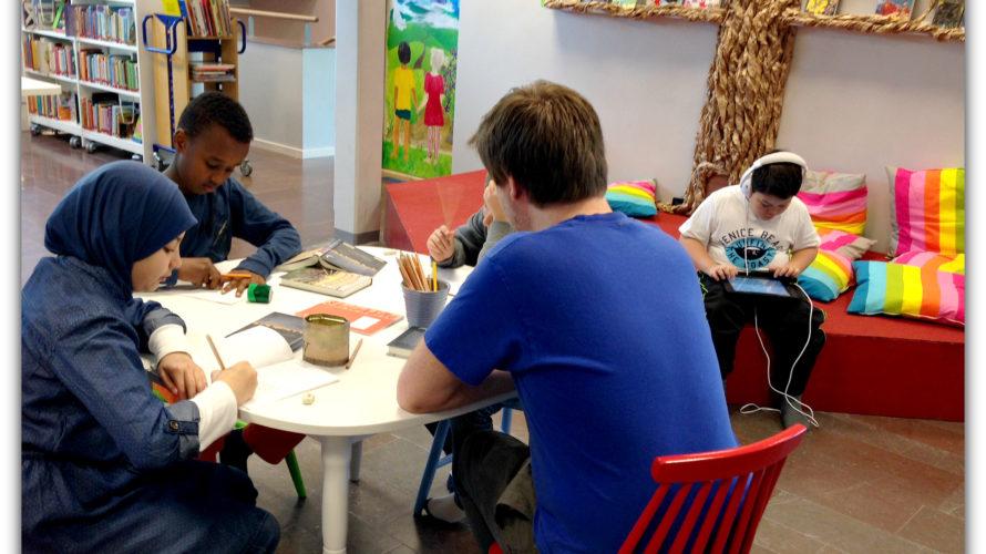 Bibliotek där barn sitter vid bord och läser och ritar.