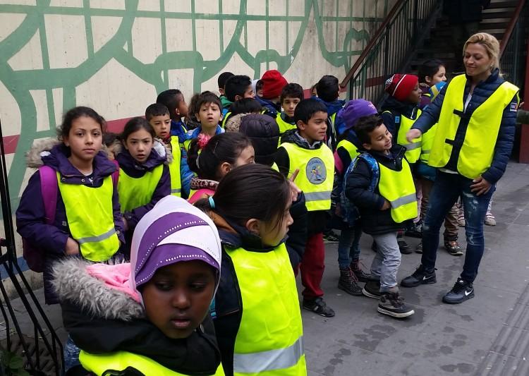 Barn i reflexvästar står samlade på gatan.