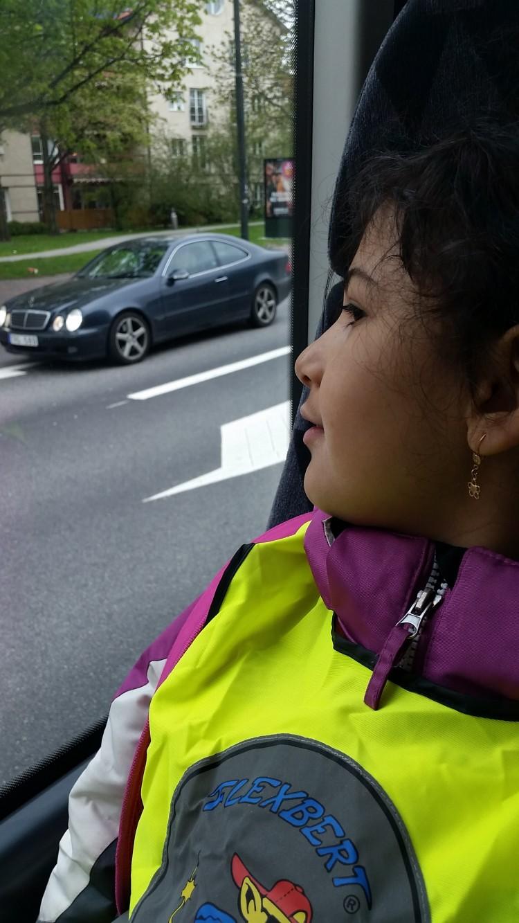 Barn i reflexvästar åker buss.